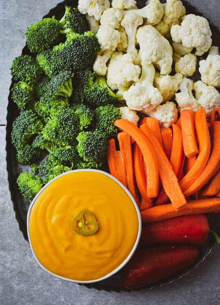 Vegan cheese sauce on veggie platter with broccoli, cauliflower, carrots, and peppers.