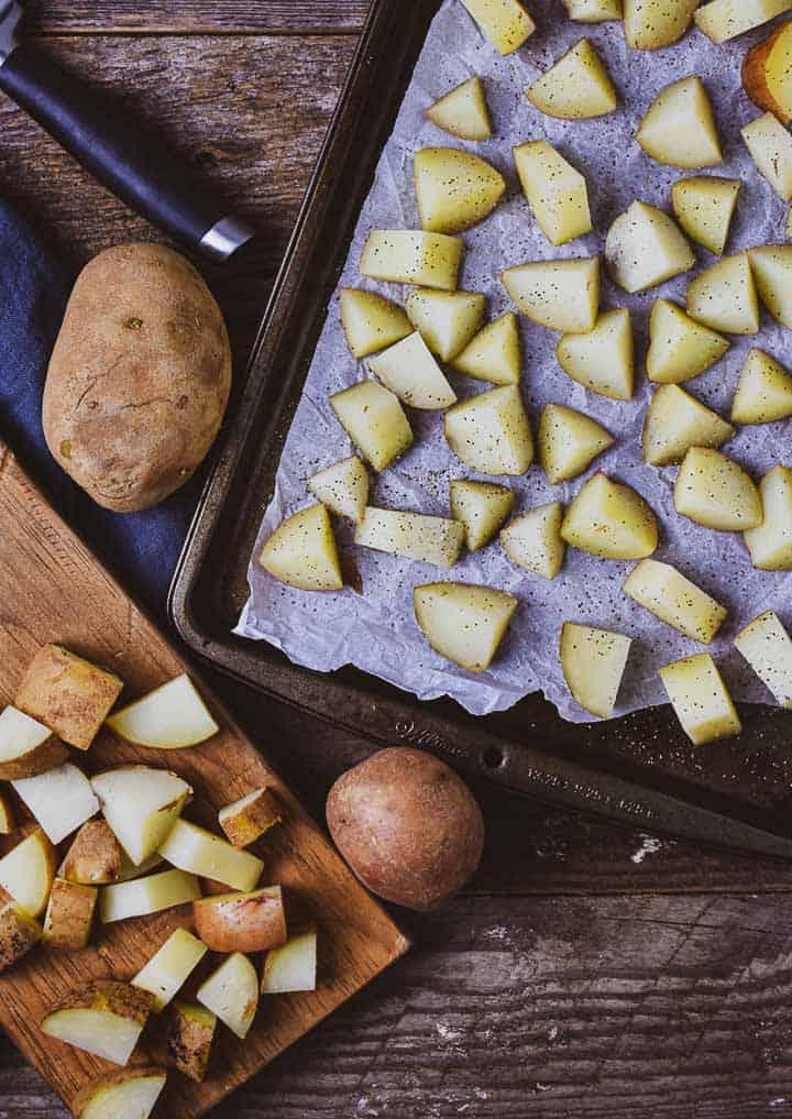 Chopped potatoes on baking sheet and cutting board.
