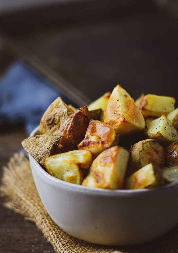 Roasted potatoes in a white bowl on burlap with baking sheet and blue napkin in the background.