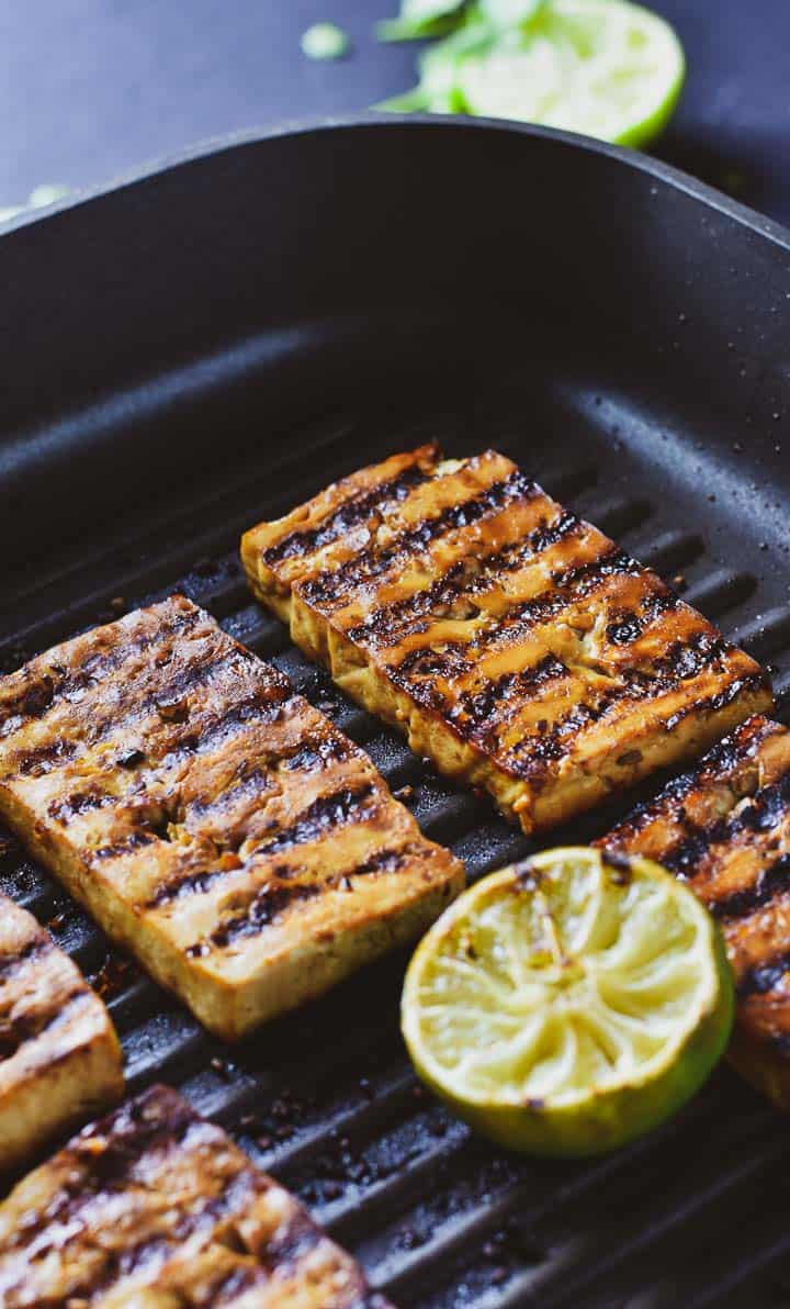 Marinated tofu in grill pan with a lime.