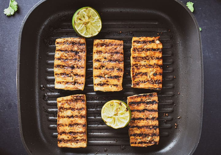 Grilled marinated tofu in grill pan with two limes.