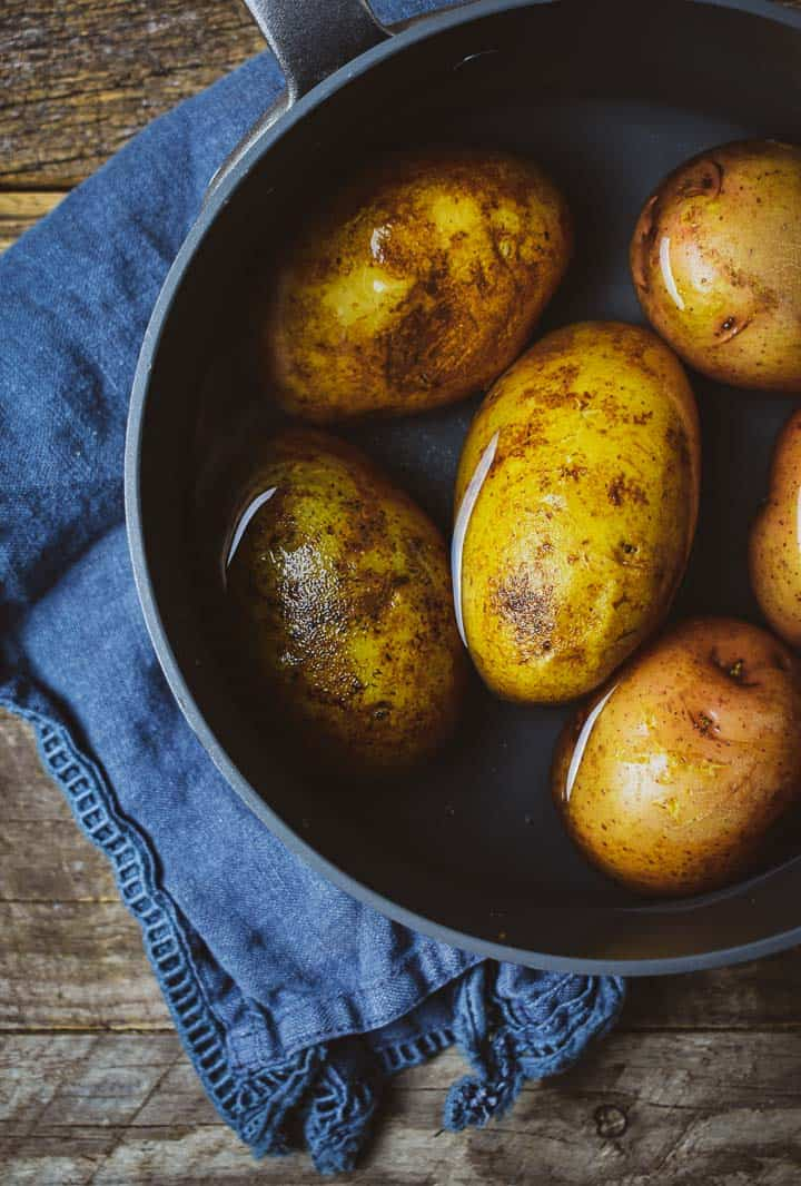 Whole potatoes in pot of water.
