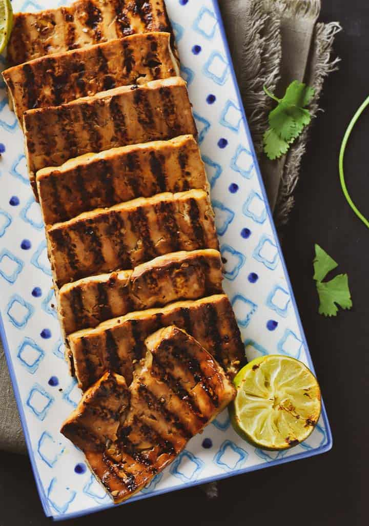 Grilled marinated tofu on serving plate with lime.