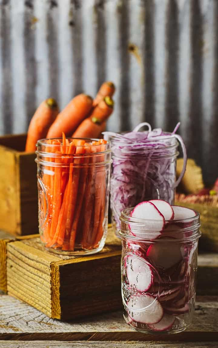 Raw carrots, onions, and radishes in jars without lids.