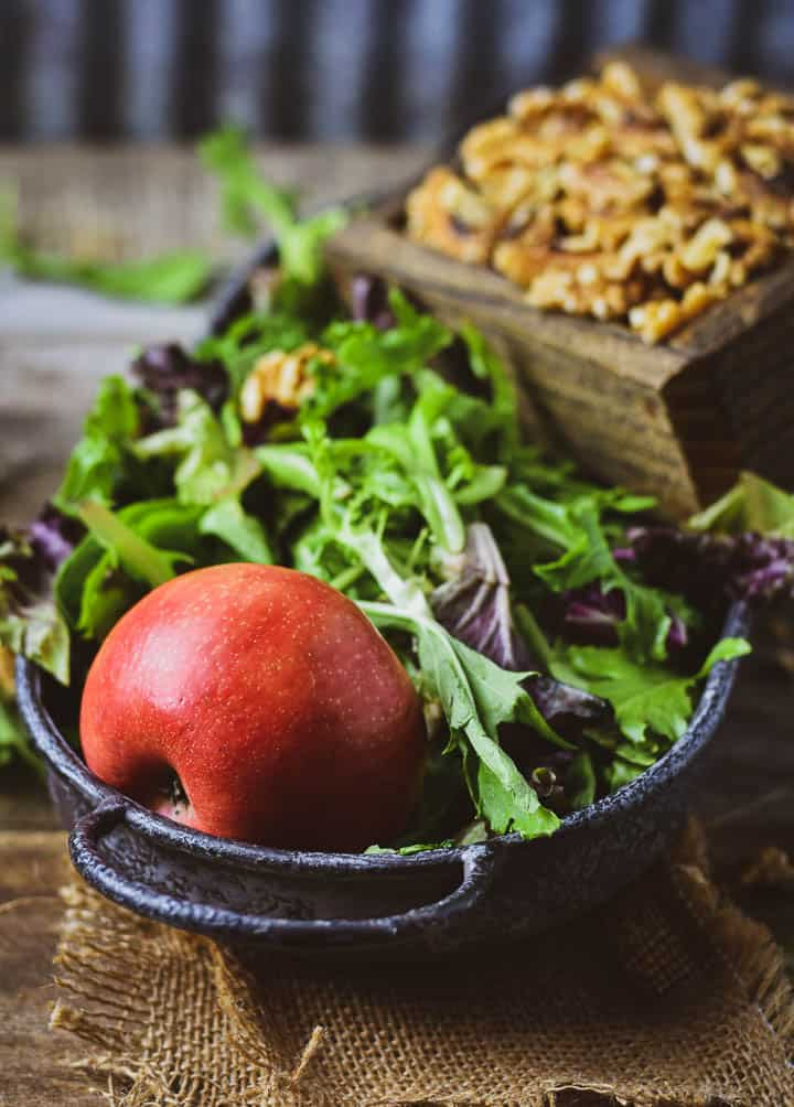 Apple in bed of salad greens with walnuts in the background.