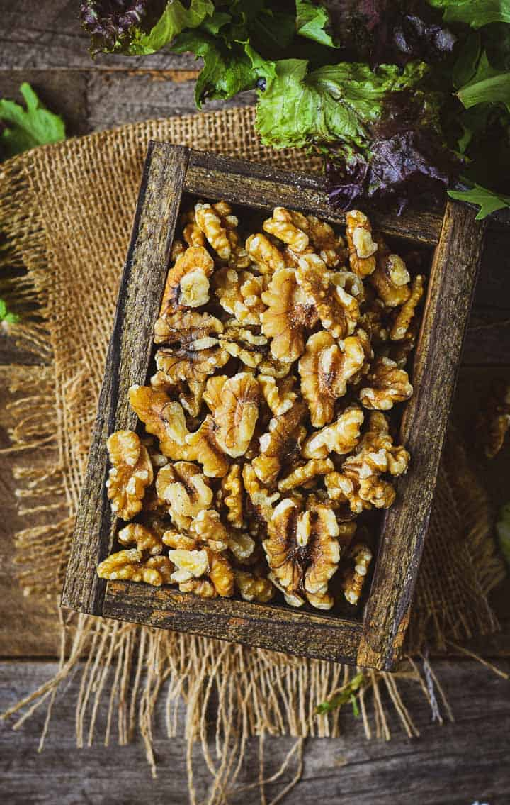 Walnuts in a wooden box on burlap with salad greens.