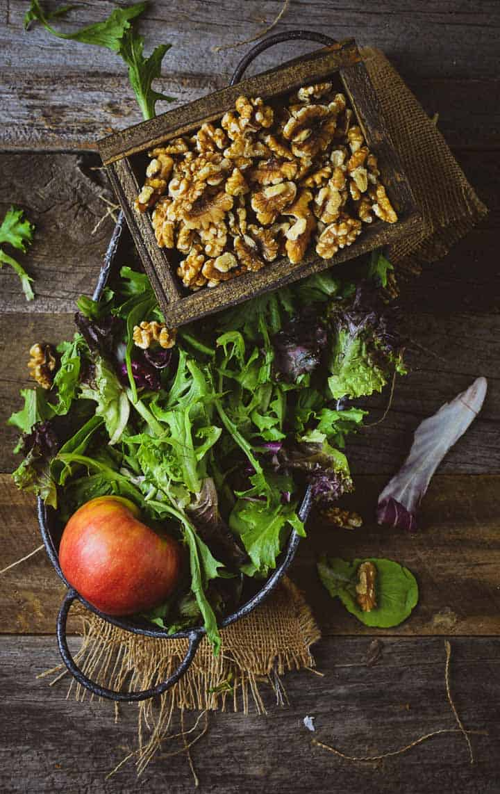 Salad greens, walnuts, and an apple in serving tray on wooden table.