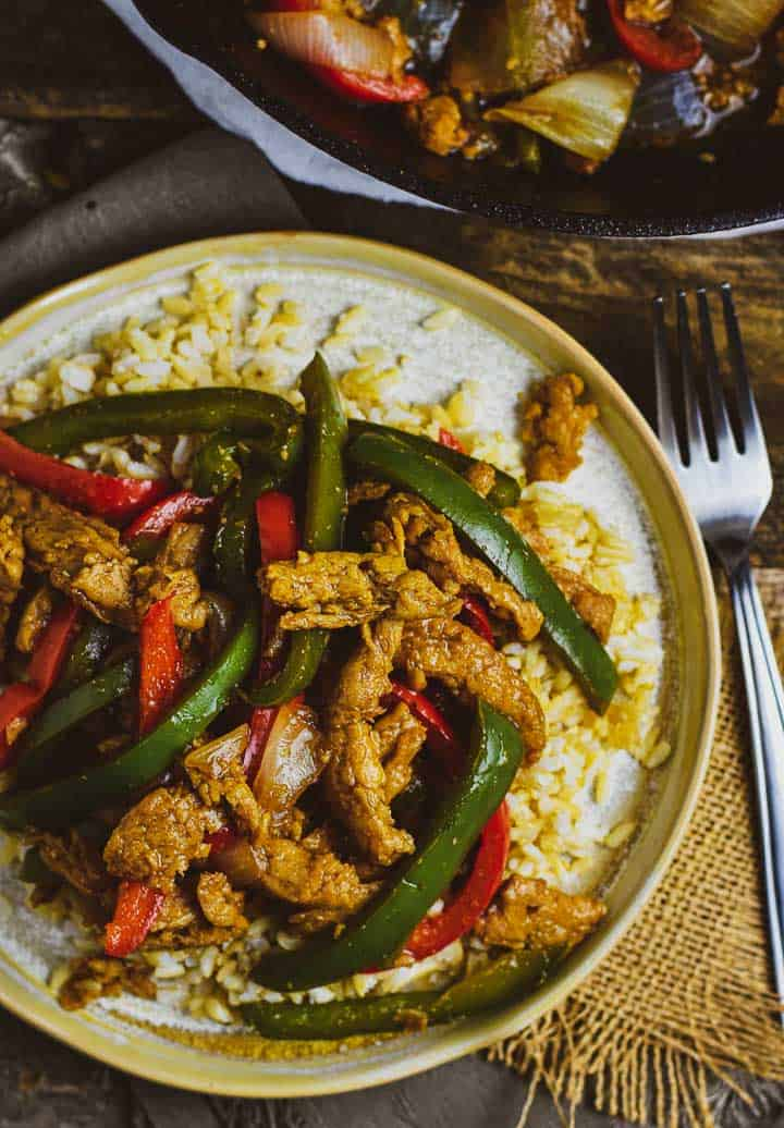 Peppers steak on plate with rice.