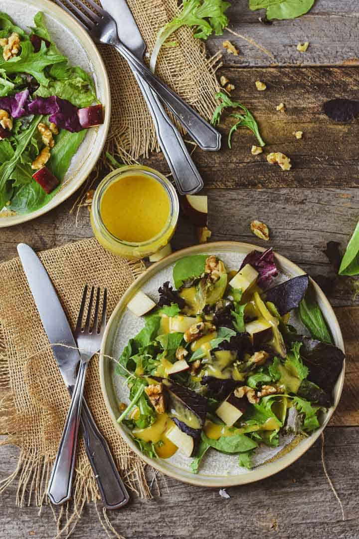 Two salads on table with vegan honey mustard dressing.