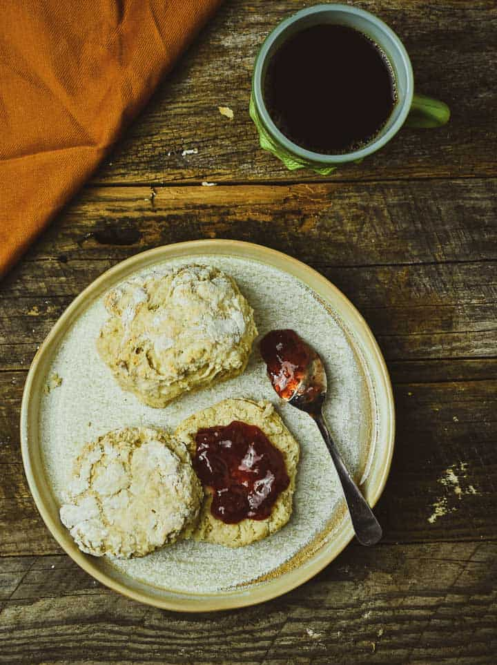 Two biscuits on plate and one with jam and cup of coffee.