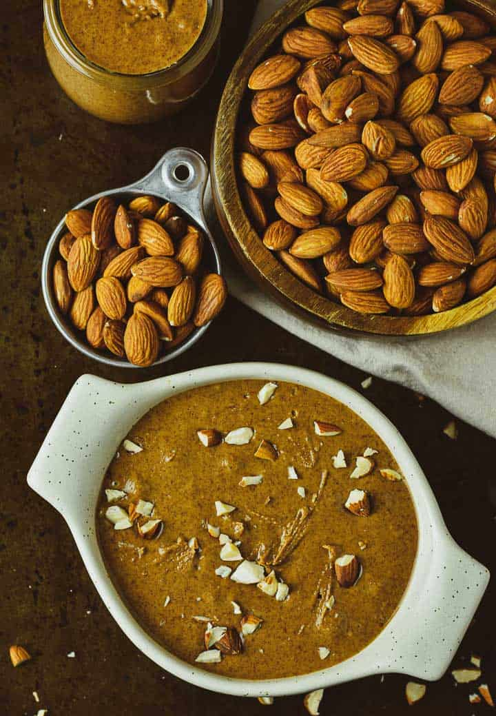 Pumpkin spice almond butter with crushed almonds and bowl of raw almonds.