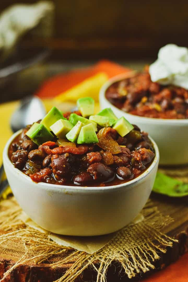 Bowl of chili with avocado on top.