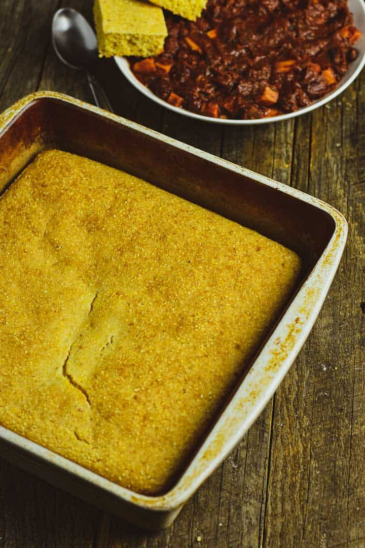 Cornbread in baking pan with chili on wooden table.