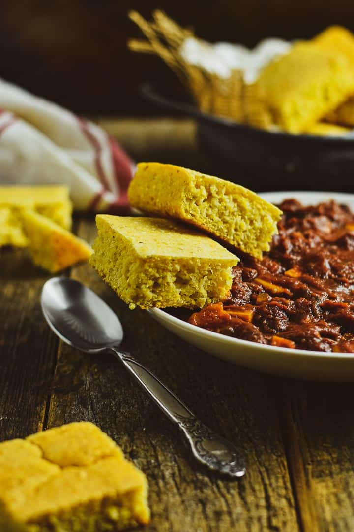 Bowl of chili and two pieces of vegan cornbread.