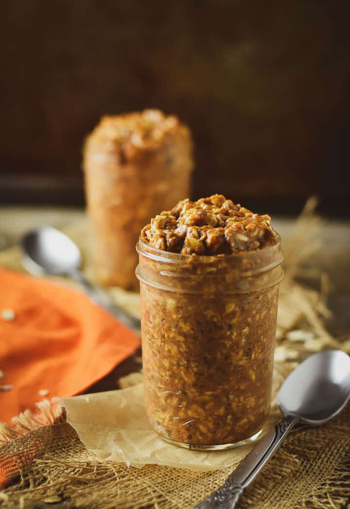 Vegan pumpkin pie overnight oats in jar on parchment paper and burlap with spoon.