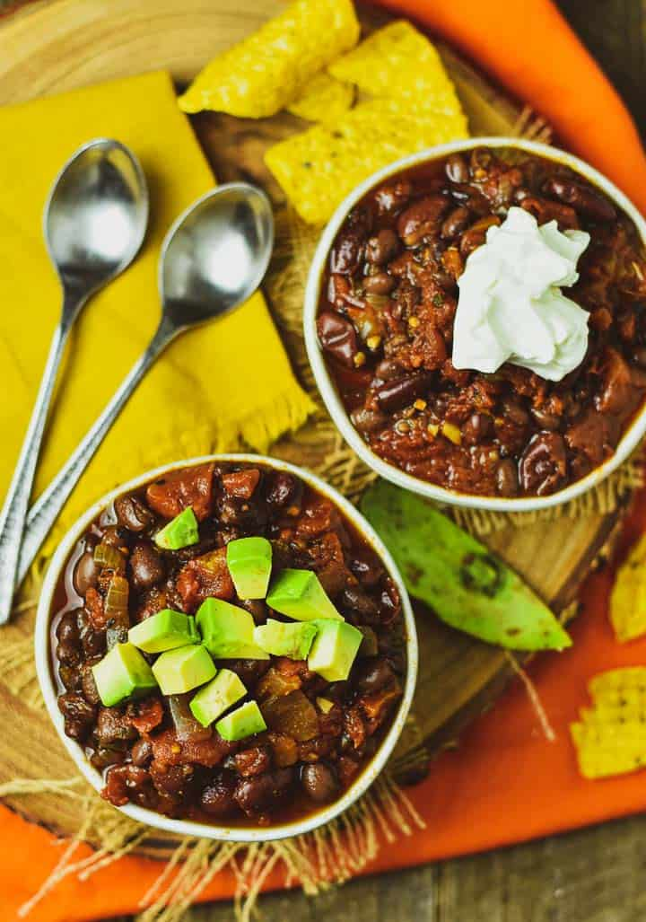 Two bowls of Instant Pot Vegan Chili with avocado and sour cream.