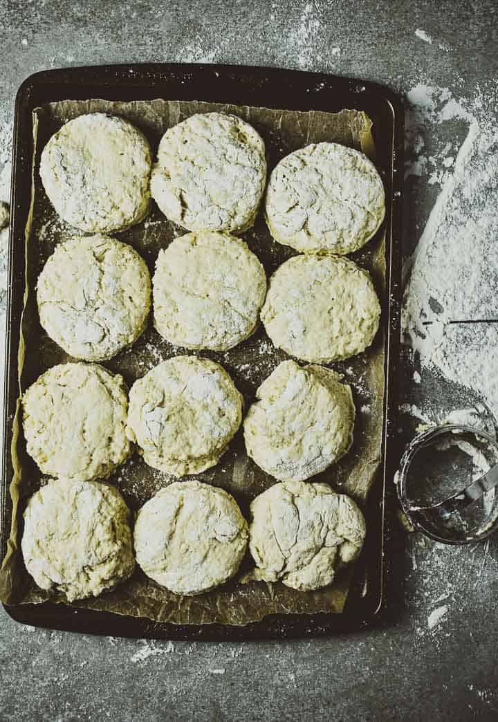 Uncooked biscuits on baking sheet with parchment paper.