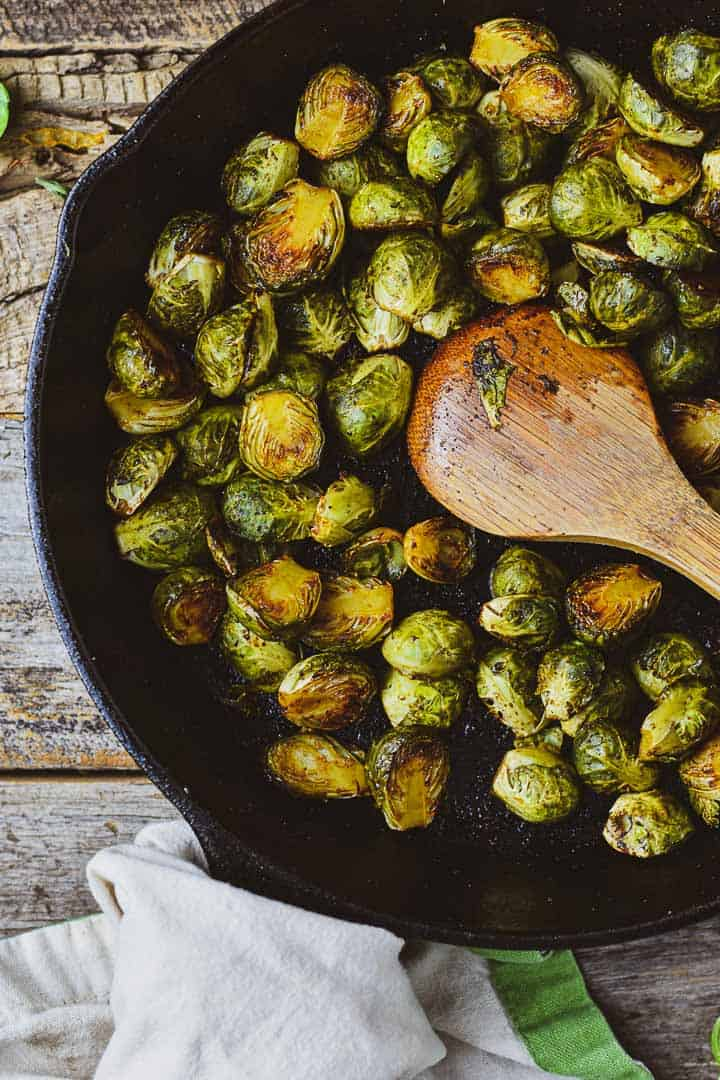 Roasted brussels sprouts in cast iron skillet with wooden spoon.