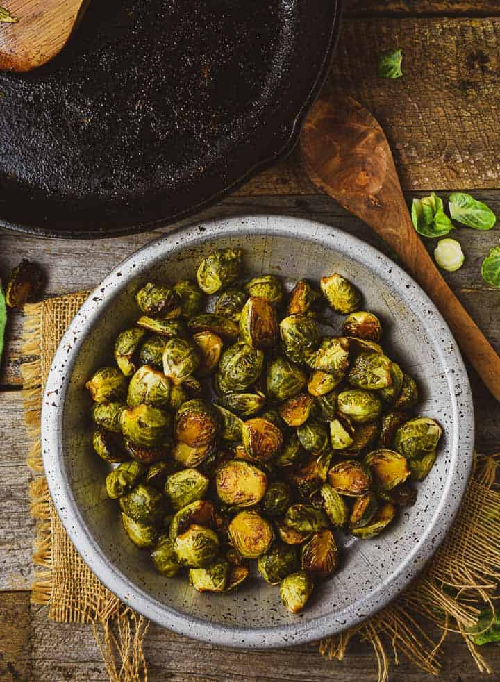 Roasted Brussels sprouts in metal bowl with wooden spoon.