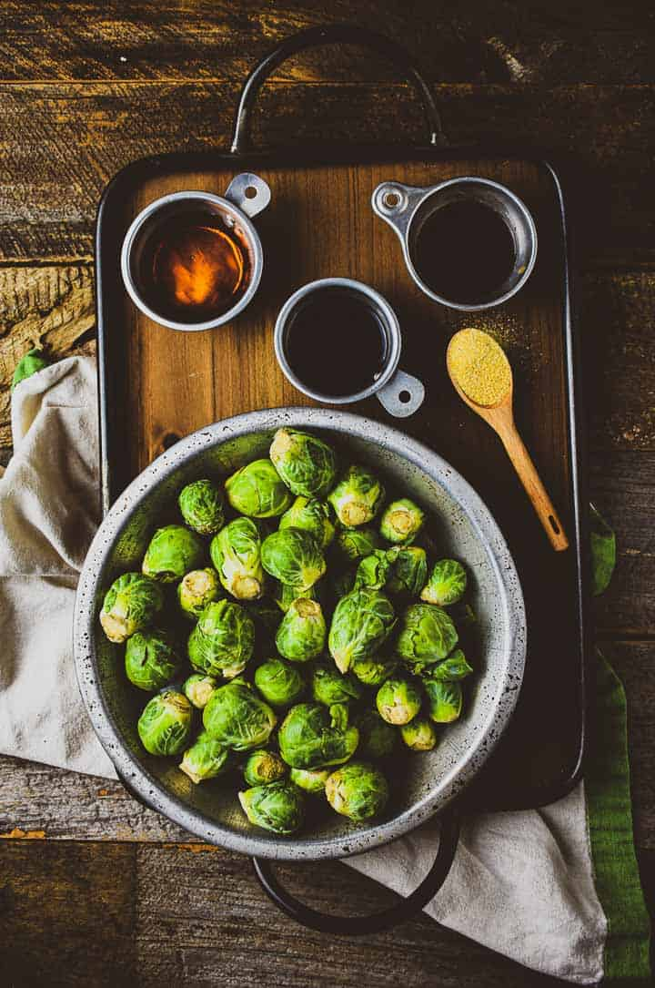 Brussels sprouts, soy, syrup, and vinegar on wooden tray.