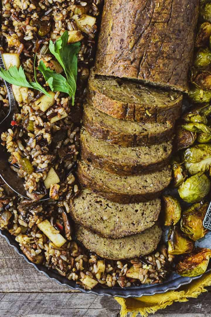 Holiday vegan roast on platter with rice and brussels sprouts.