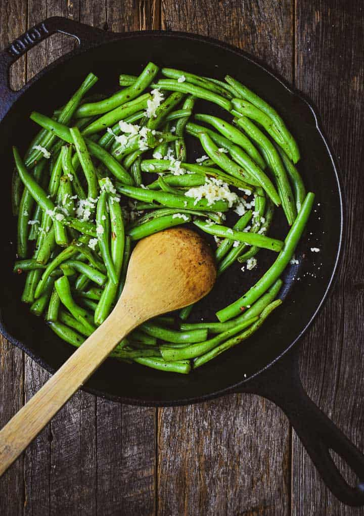 Green beans in cast iron skillet with garlic and wooden spoon.