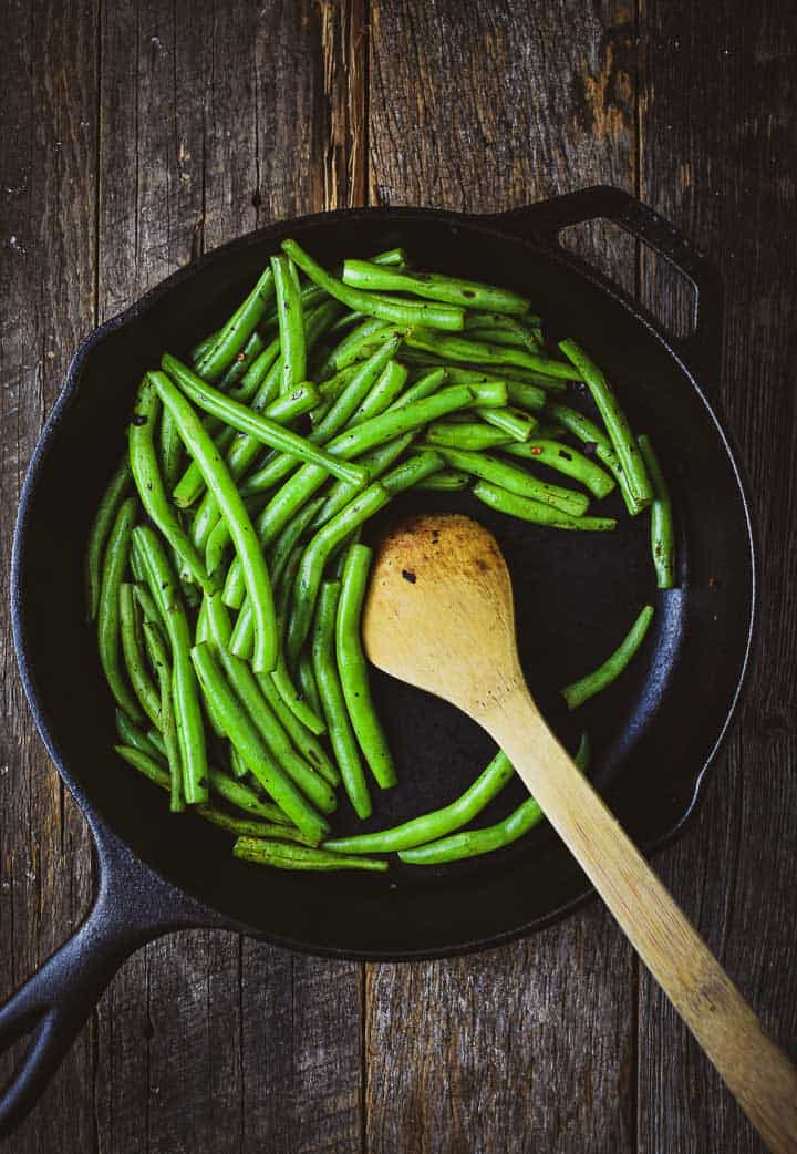 Green beans in cast iron skillet with wooden spoon.