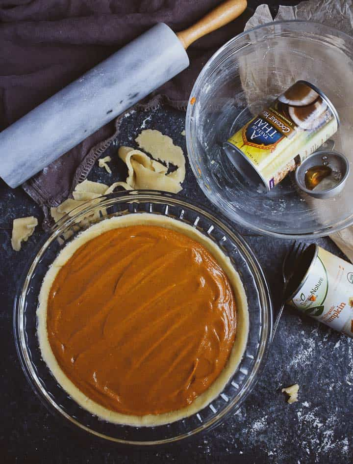 Pumpkin pie filling in pie dish with mixing bowl.