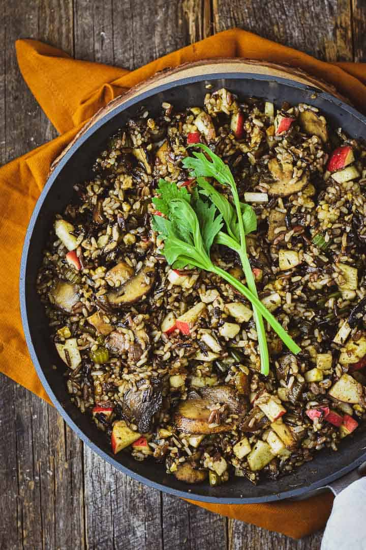 Vegan wild rice stuffing in pan with garnish.
