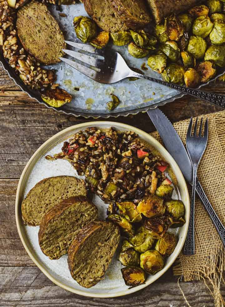 Vegan roast on plate with brussels sprouts and wild rice.