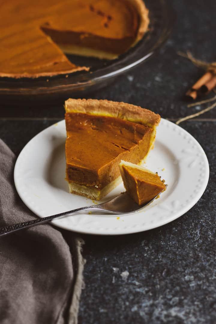 Vegan pumpkin pie on plate with fork.