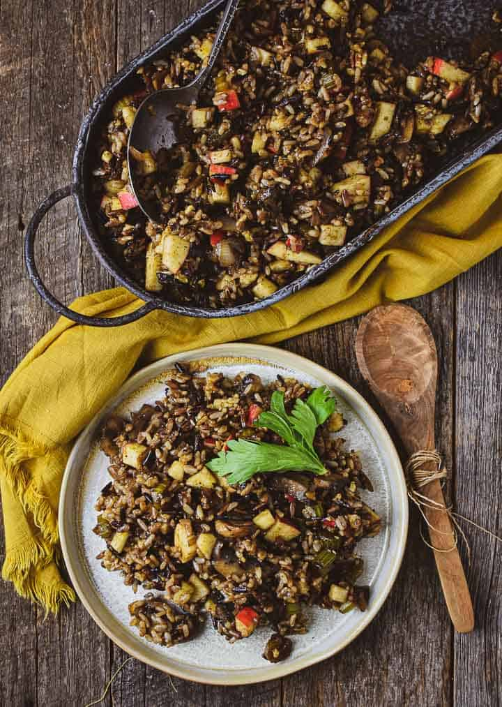 Wild rice stuffing on plate and serving platte with wooden spoon.