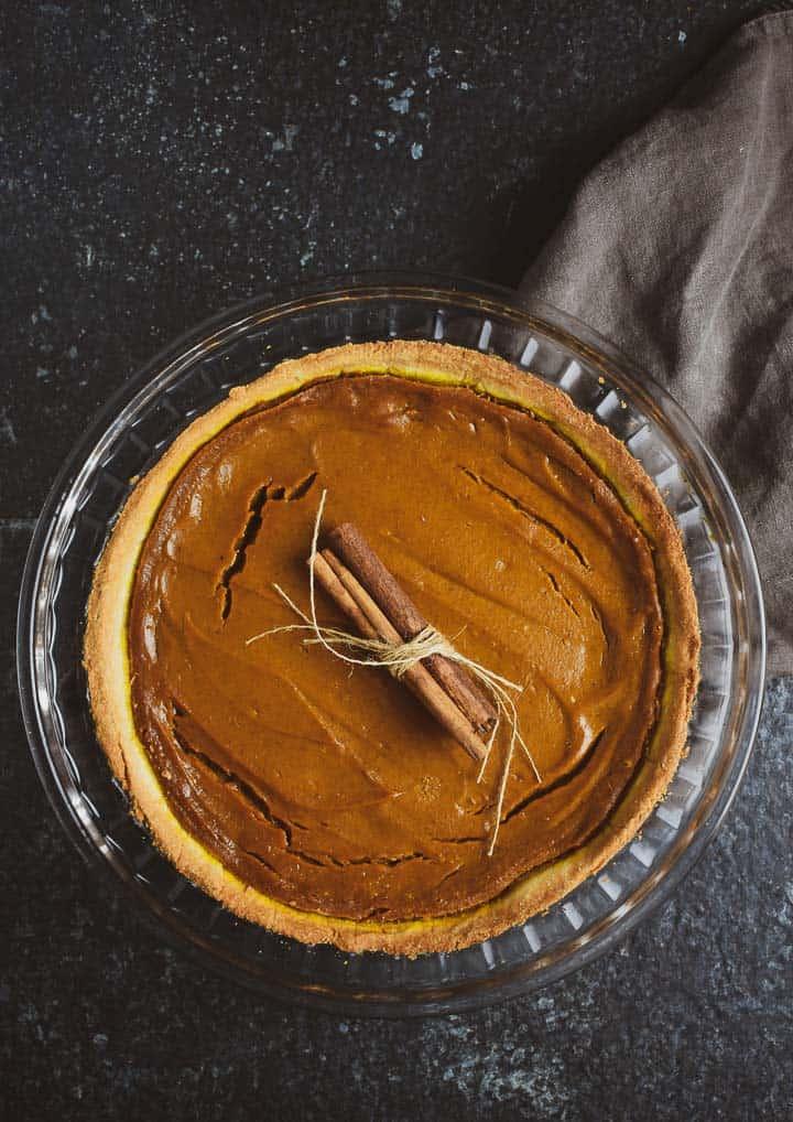 Vegan pumpkin pie in pie dish with cinnamon sticks on top.