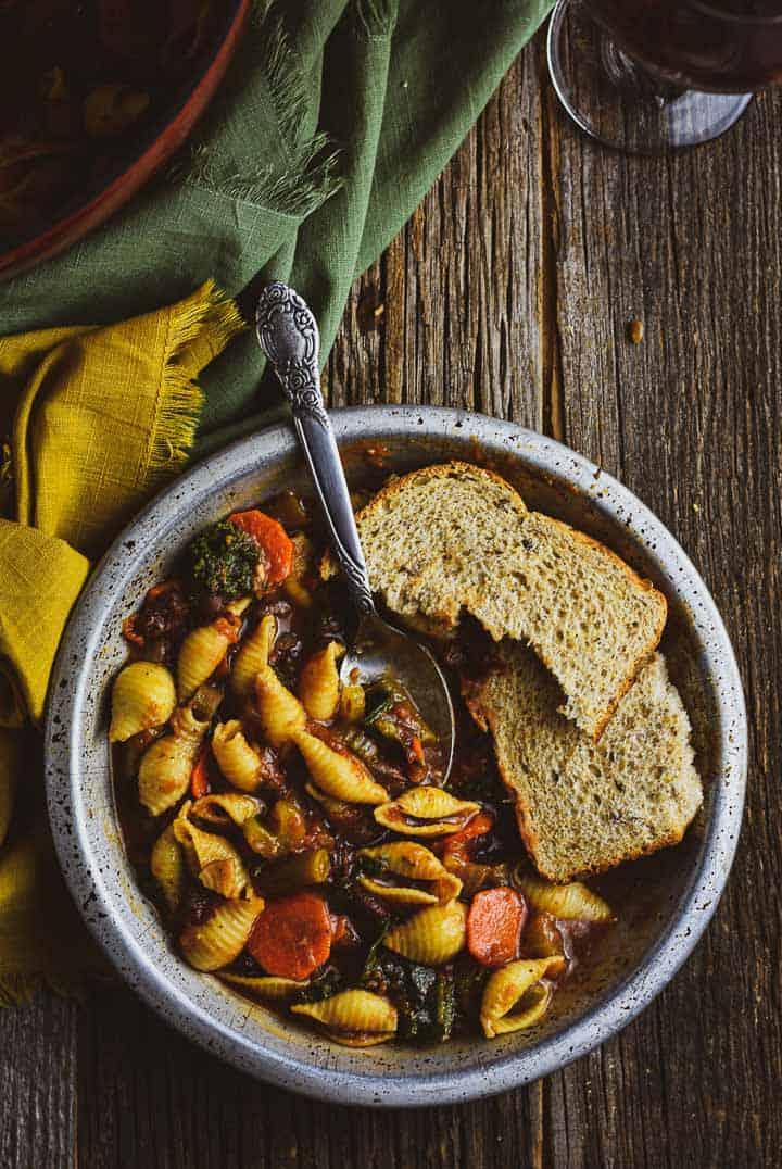 Vegan minestrone soup in bowl with spoon and bread.