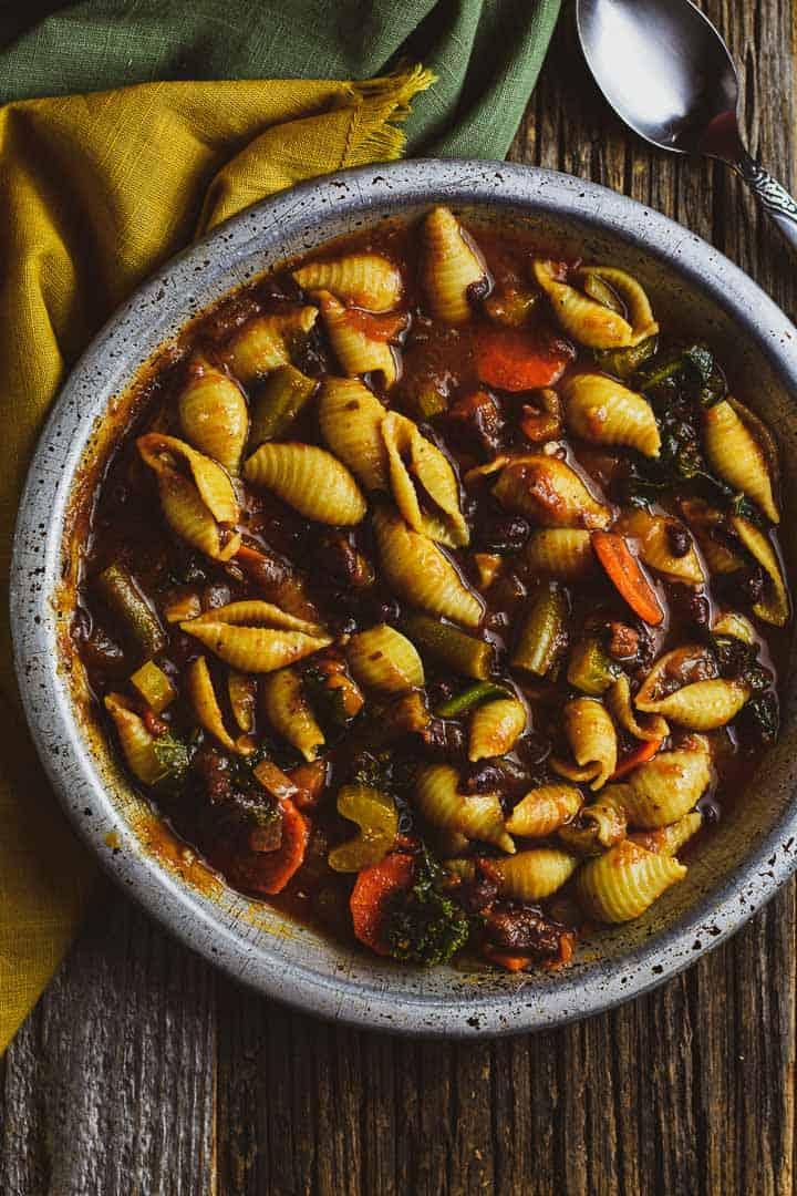 Vegan minestrone soup in sliver bowl.