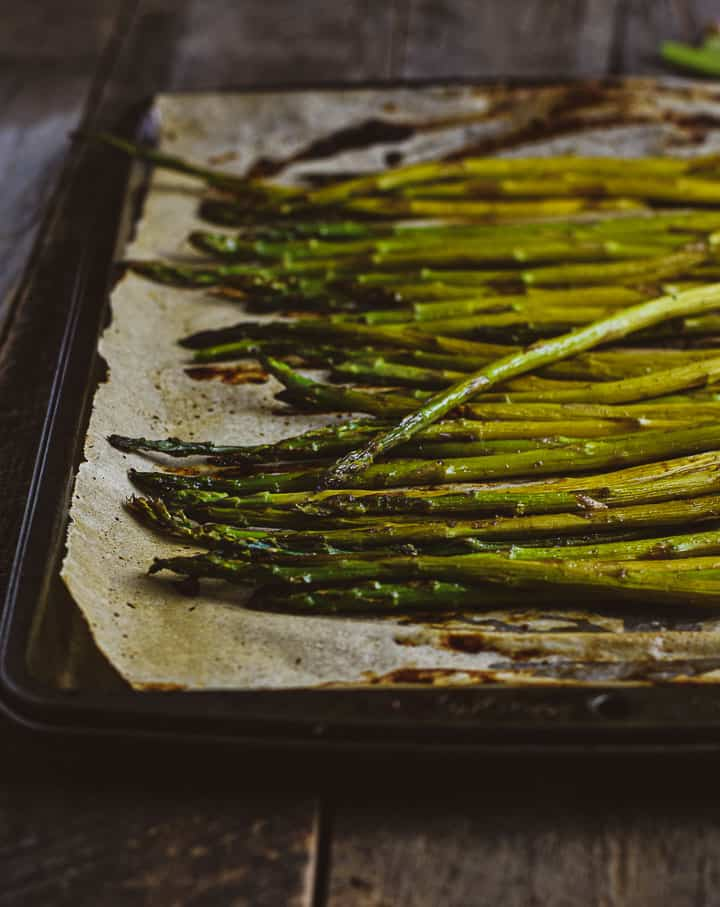 Oven roasted asparagus on baking sheet.