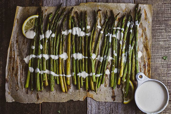 Oven roasted asparagus on parchment paper with lemon tahini sauce in cup.