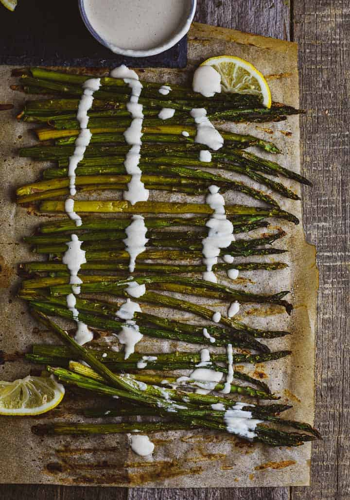 Oven roasted asparagus on parchment paper with lemon tahini sauce.