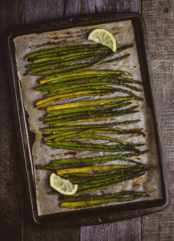 Oven roasted asparagus on baking sheet with parchment paper and lemons.