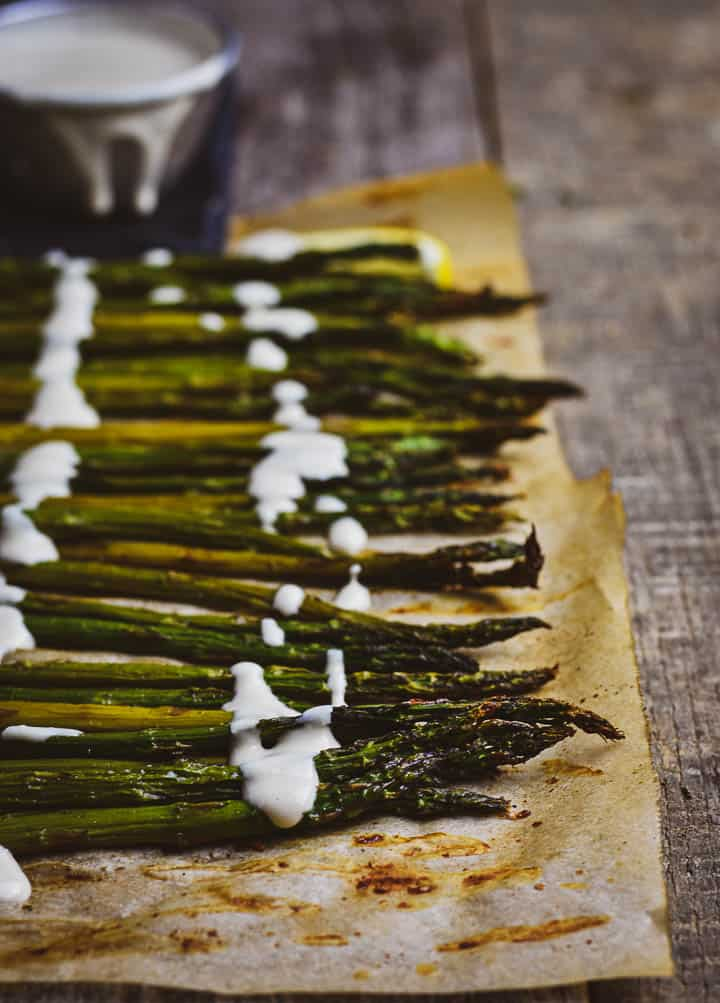 Roasted asparagus on parchment paper with lemon tahini sauce drizzled on top.