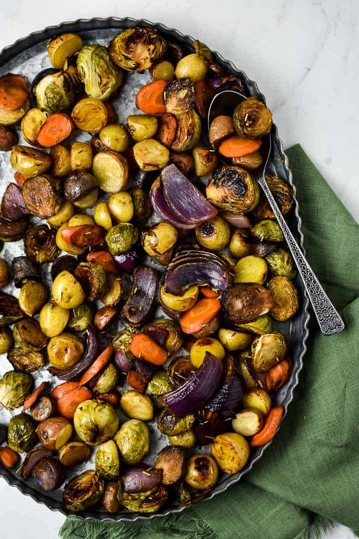 Oven roasted vegetables on tray with a spoon.