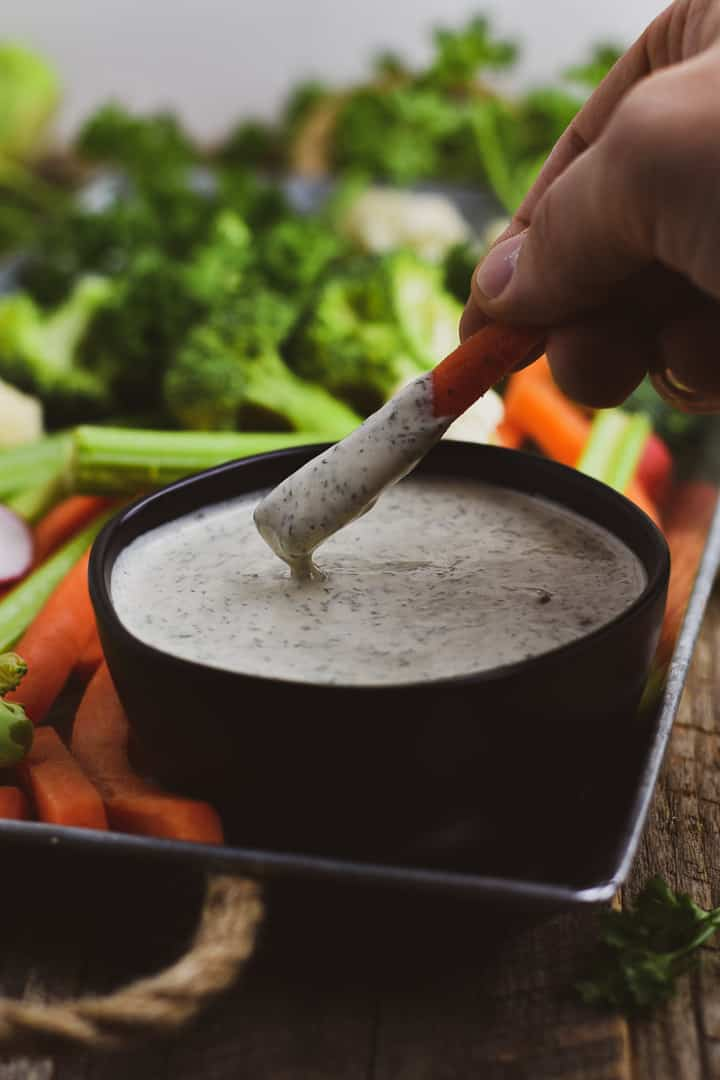 Carrot stick being dipped in ranch dressing.