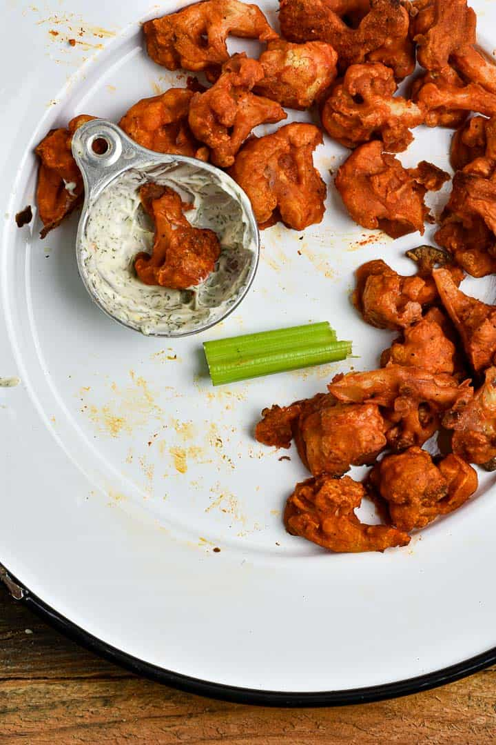 Vegan buffalo cauliflower on platter with celery and dipping sauce.