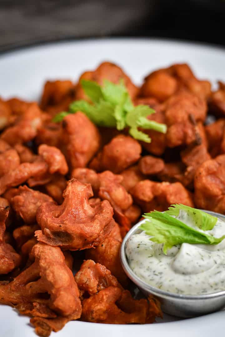 Buffalo cauliflower on serving platter with ranch dressing.