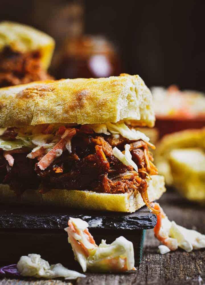 Vegan pulled pork sandwich with slaw on slate.