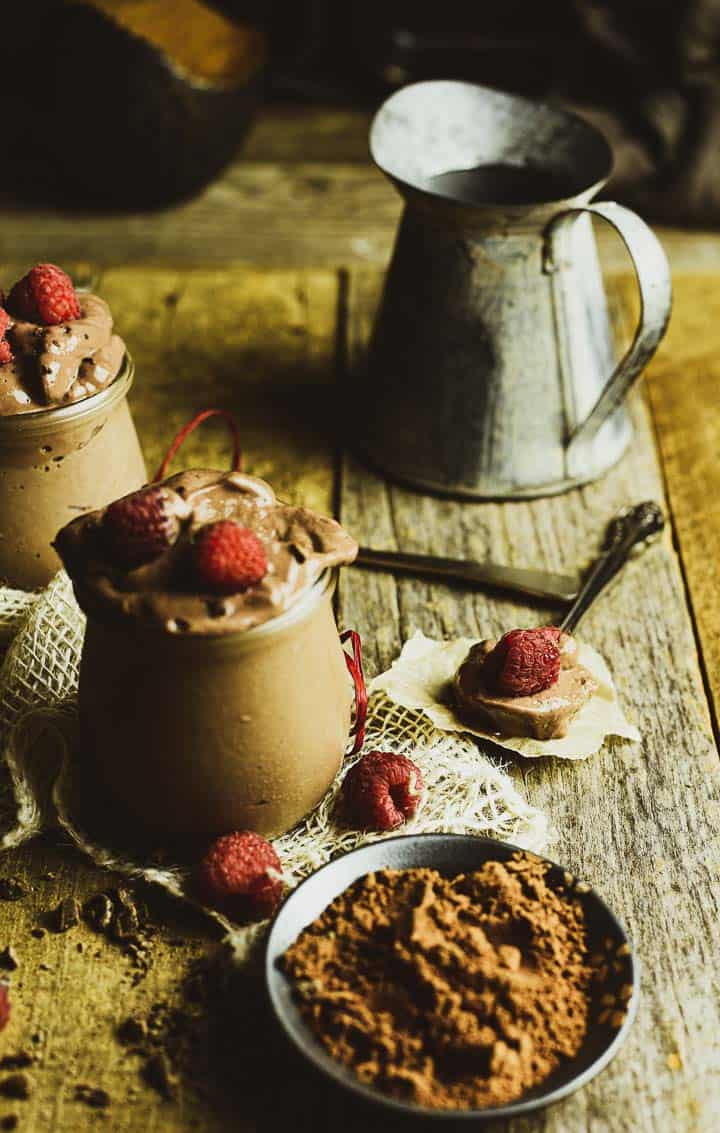 spoon with chocolate mousse on table with raspberries