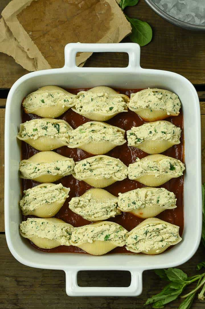 Vegan stuffed shells with tofu ricotta in baking dish before being cooked.