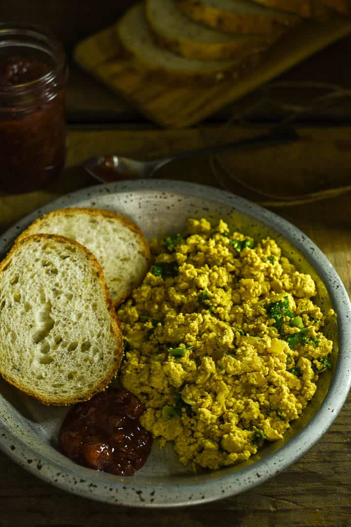 Vegan tofu scramble in tin plate with two pieces of toast.