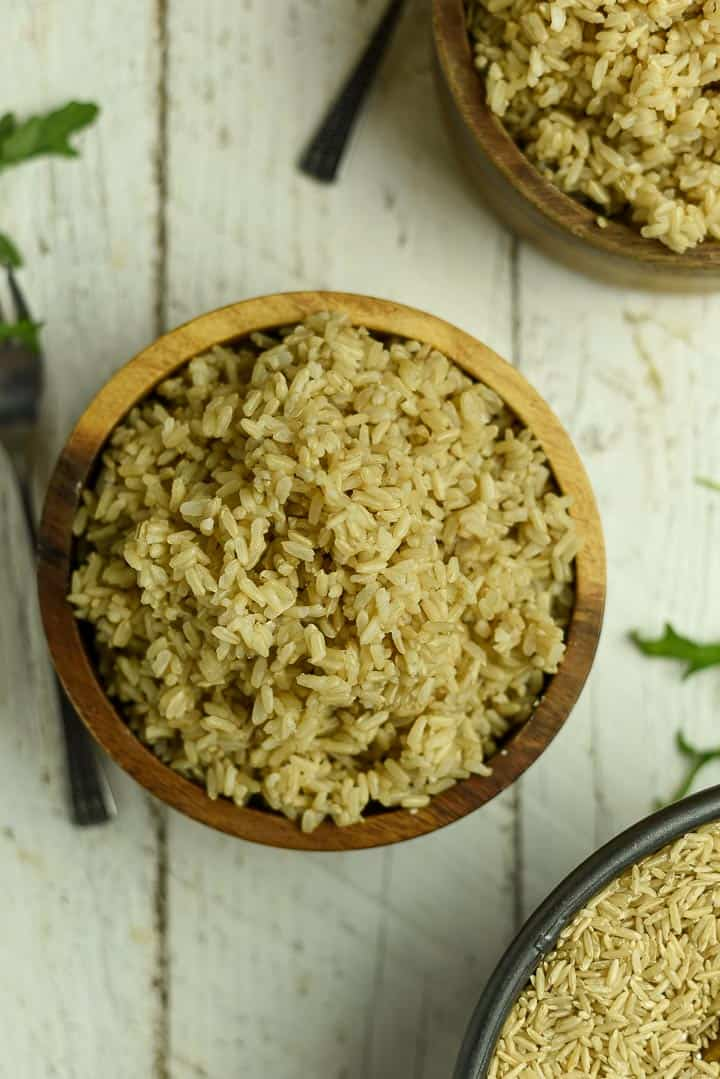 Cooked brown rice in wooden bowl.
