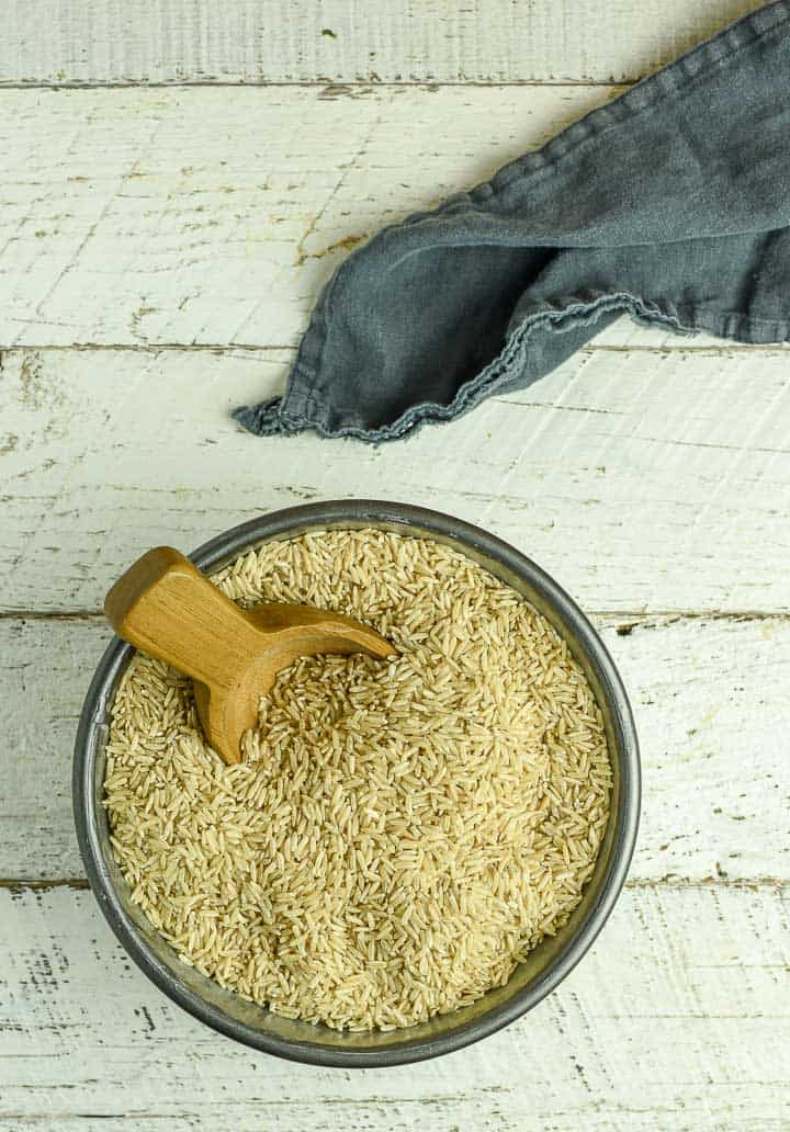Dry brown rice in bowl with wooden scoop.